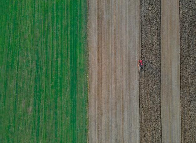 Rode tractor met in een veld om land luchtfoto op van landbouwgebied te ploegen