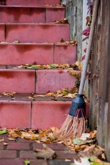 Rode treden met gele bladeren, bezem, tuin schoonmaken.