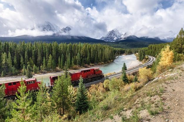 Rode trein lange vracht op spoorweg die in de herfstvallei overgaat en boogrivier bij morant-kromme