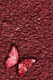 Rode tropische vlinder zit op rode rotsachtige muur. hoge kwaliteit foto