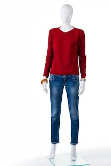 Rode trui en blauwe spijkerbroek. vrouwelijke ledenpop die rode sweater draagt. herfst kleding op winkel showcase. kortingen voor nieuwe merchandise.