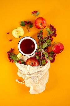 Rode tuin biologische appels, meidoornbessen in een netzak en kopje hete gekruide thee op een oranje achtergrond. herfst stilleven plat.