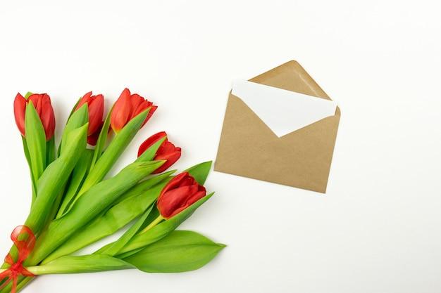 Rode tulpen en een blanco brief in een bruine envelop liggen op een witte tafel. mockup