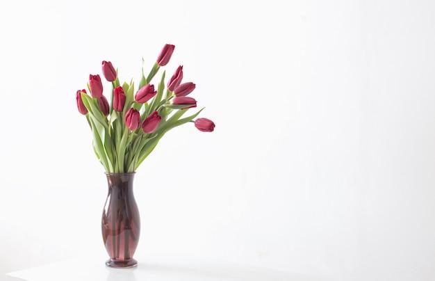 Rode tulpen in glasvaas op wit oppervlak