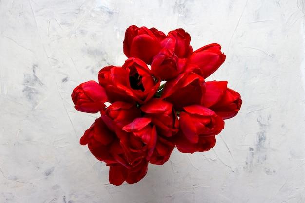 Rode tulpen in het midden van de afbeelding op een lichte stenen ondergrond. kopieer ruimte. plat lag, bovenaanzicht