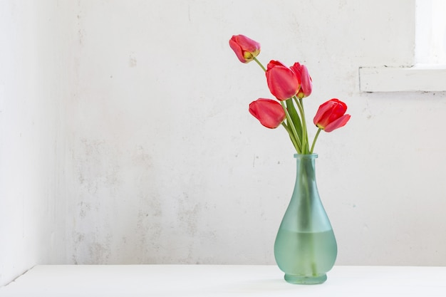 Rode tulpen in vaas op witte tafel