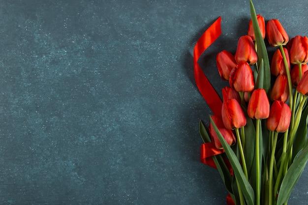 Rode tulpen op blauw, briefkaart leeg, lentevakantie, moederdag. kopieer ruimte.