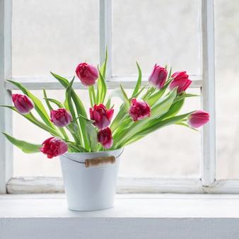 Rode tulpen op oude witte vensterbank