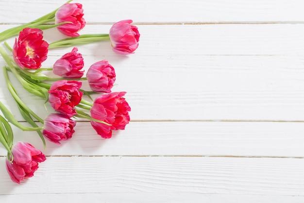 Rode tulpen op witte houten achtergrond