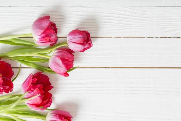 Rode tulpen op witte houten oppervlak