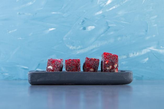 Rode turkse lekkernijen in een houten bord, op het marmeren oppervlak