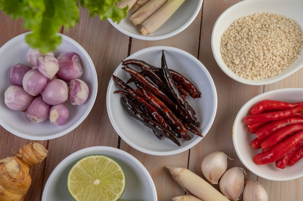 Rode uien, citroen, citroengras, pepers, knoflook, laos en sla in een kopje op een houten vloer.