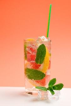 Rode verse drank met ijs, grapefruit en munt op een oranje muur. ruimte voor tekst of ontwerp.
