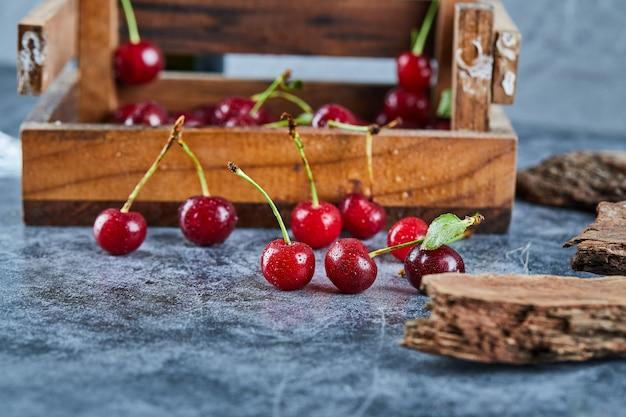 Rode verse, sappige kersen in een houten doos met bladeren