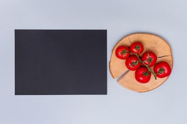Rode verse tomaat op boomstomp dichtbij zwarte staat over grijze achtergrond