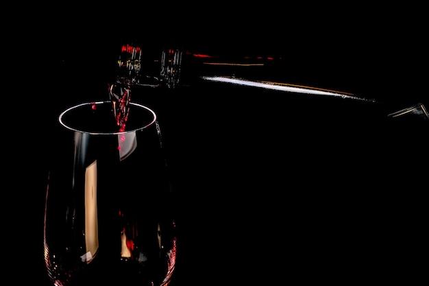 Rode versterkte wijn wordt gegoten in een glazen beker kunst fotografie op een zwarte achtergrond close-up
