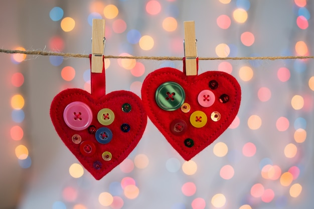 Rode vilten harten ambachten versierd met kralen en knopen met lichten. valentijnsdag decor.