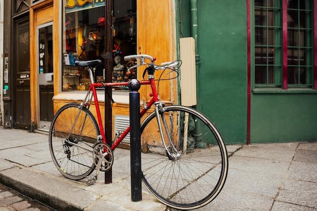 Rode vintage fiets geparkeerd op de straat in de stad. stedelijke scène.
