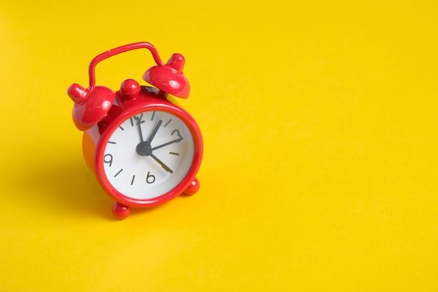 Rode vintage klok op een gele achtergrond aan de linkerkant.