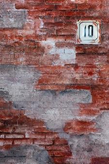 Rode vintage stijlvolle bakstenen muur met huisnummerplaat 10