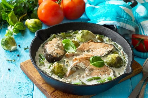 Rode vis en groenten gebakken spruitjes sperziebonen in roomsaus in een koekenpan