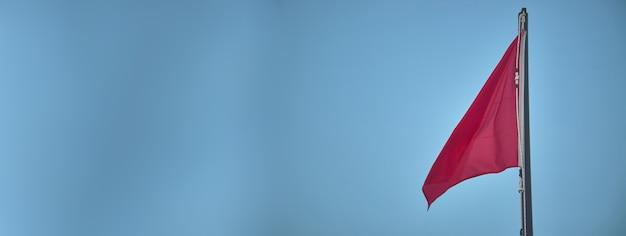 Rode vlag banner detail onder een blauwe lucht
