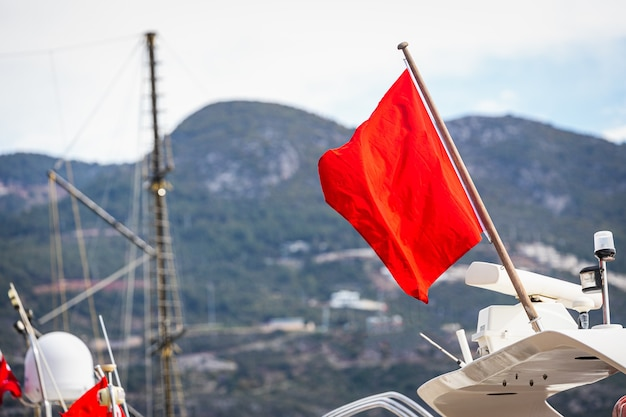 Rode vlag zwaaien bevestigd aan een wit jacht tegen de achtergrond van de jachthaven en de zee