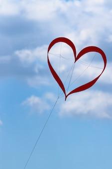 Rode vlieger in de vorm van een hart in de blauwe lucht met wolken voor valentijnsdag