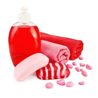 Rode vloeibare zeep in een fles, stevige rood gestreepte en roze zeep, badzout, twee handdoeken die op wit worden geïsoleerd