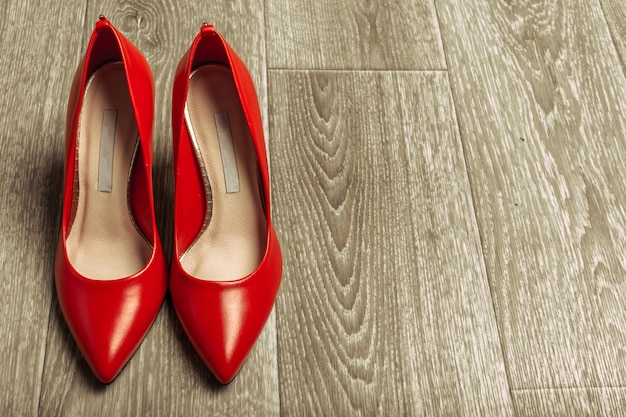 Rode vrouwenschoenen op houten oppervlakte