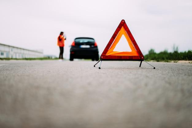 Rode waarschuwingsdriehoek op de voorgrond op de weg. meisje in het reflecterende vest op de achtergrond.