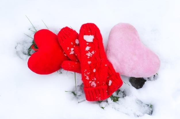 Rode wanten, papieren hondenfiguren en groene dennenboomtakken in houten decoratieve doos op sneeuw.