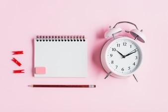 Rode wasknijper; spiraal notitieblok; rubber; potlood en wekker tegen roze achtergrond