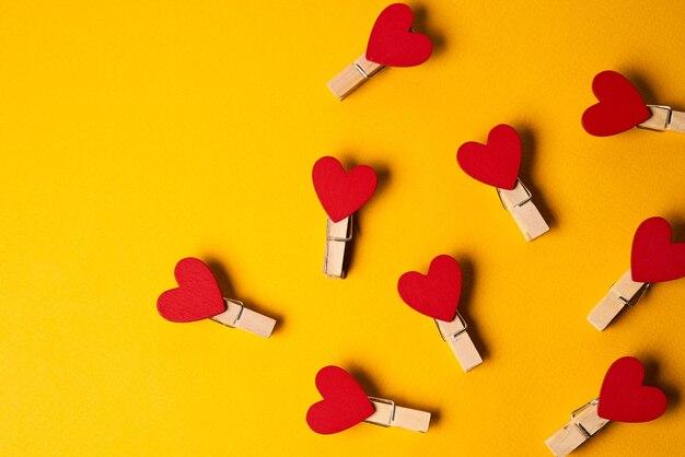 Rode wasknijpers in de vorm van harten op een gele achtergrond close-up en aantal items