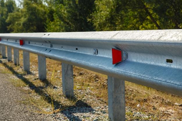 Rode wegreflectoren langs de weg. metalen weghekken van het type barrière. verkeers- en verkeersveiligheid