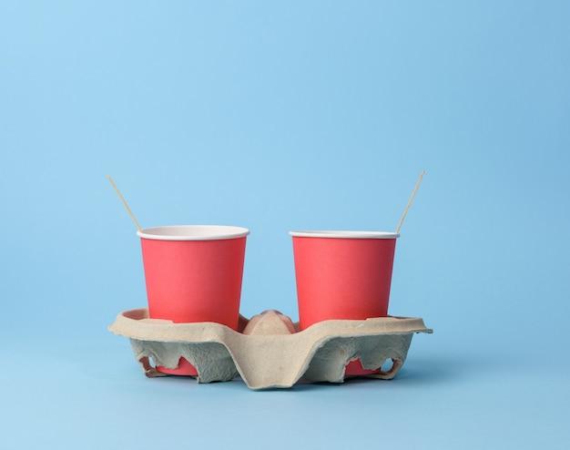 Rode wegwerpbekers in papierhouder op blauwe achtergrond, afwijzing van plastic, nul afval