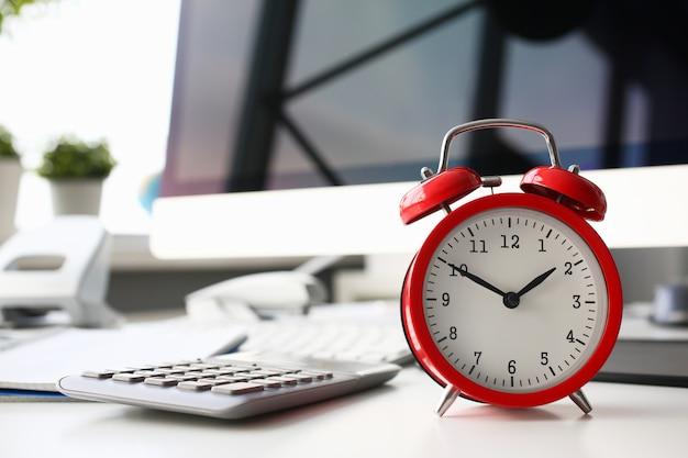 Rode wekker die op acht in de ochtendclose-up wordt geplaatst