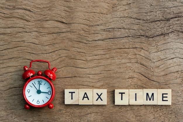 Rode wekker en belastingtijd met houten alfabetblokken, op plank houten achtergrond met exemplaarruimte