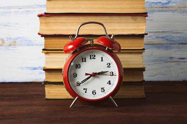 Rode wekker en een stapel boeken op een houten oppervlak