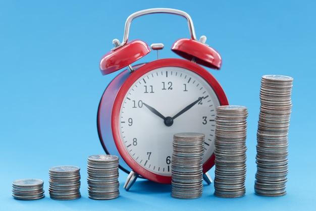 Rode wekker en piramide van munten. tijdbeheer in bedrijfsconcept