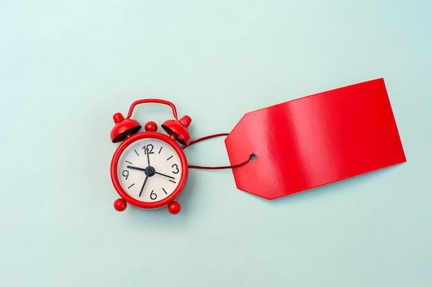 Rode wekker en rood label blanco voor een inscriptie op een blauwe achtergrond