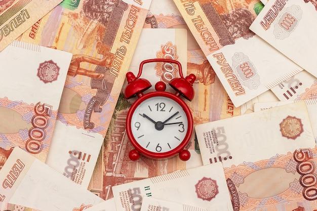 Rode wekker op de achtergrond van russische vijfduizendste rekeningen. concepttijd is geld