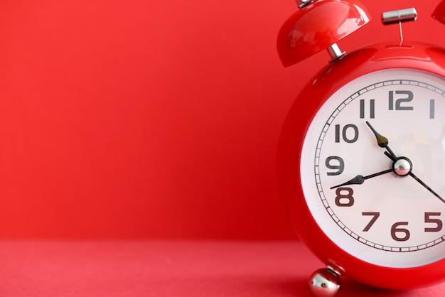 Rode wekker op rode achtergrond tijdbeheer in bedrijfsconcept