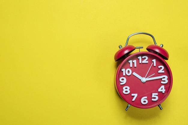 Rode wekkerbeelden die op een gele achtergrond, tijdconcept worden geplaatst met exemplaarruimte