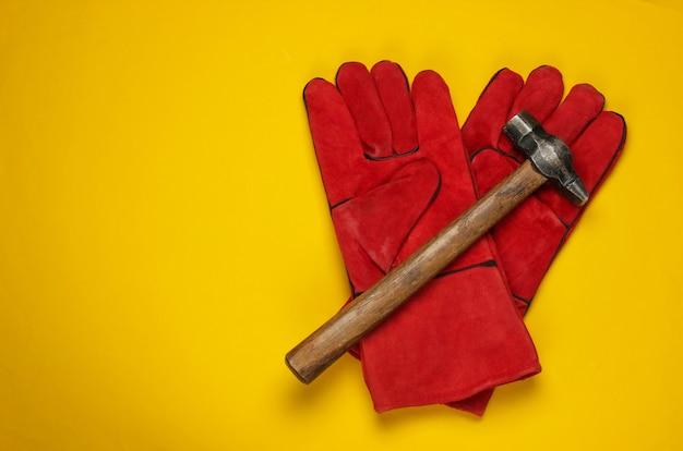 Rode werkhandschoenen, hamer gele achtergrond. bouwer tool. bovenaanzicht
