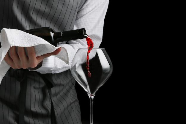 Rode wijn die door de barman in glas wordt gegoten