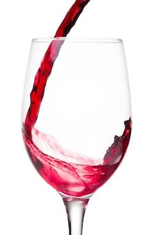 Rode wijn die in een glas wordt gegoten dat op witte muur wordt geïsoleerd