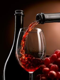 Rode wijn die in een glas wordt gegoten