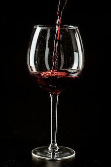 Rode wijn die in een wijnglas op dark wordt gegoten