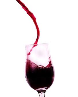 Rode wijn die in het glas stroomt